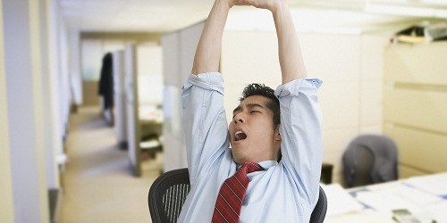 Korean businessman yawning and stretching in office