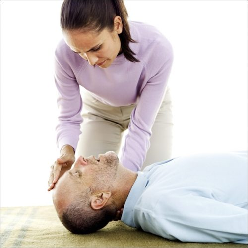 Young Woman Laying an Elderly Man Down on the Floor --- Image by © Royalty-Free/Corbis